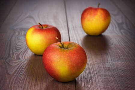 fresh red apples on the brown wooden table photo