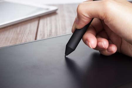 de hand van de ontwerper met een pen op tablet