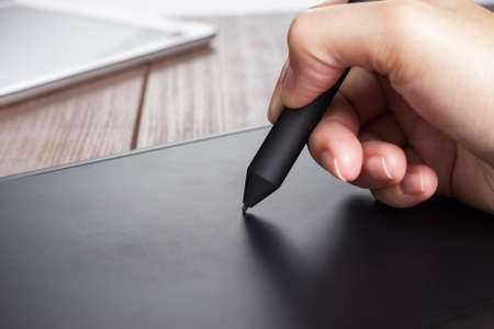 hand of the designer with a pen on tablet Stock Photo