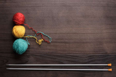 yarn: knitting needles and colorful ball of threads on wooden background Stock Photo