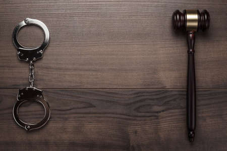 handcuffs and judge gavel on brown wooden background Stock Photo