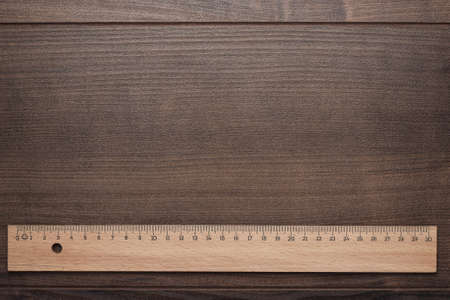 wood ruler on the brown wooden background