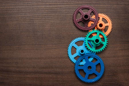 colorful gears on the brown wooden background photo
