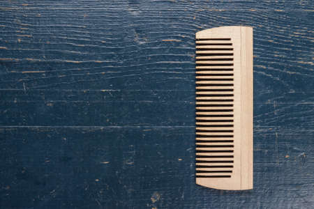 handmade wooden comb on the blue table photo
