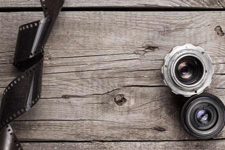 Retro-Kamera-Objektive und Negativfilm auf Holztisch