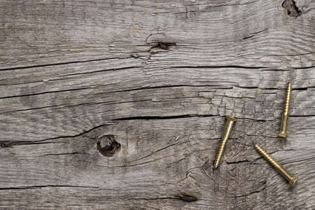new yellow screws on the wooden table background Stock Photo