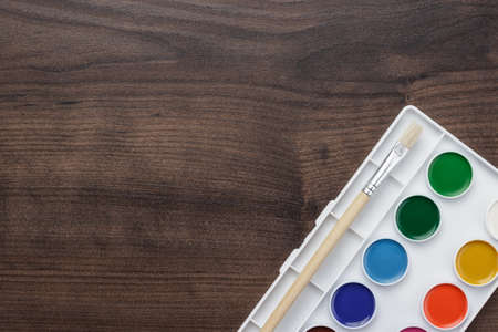 palette with paint and brush on the wooden table background photo