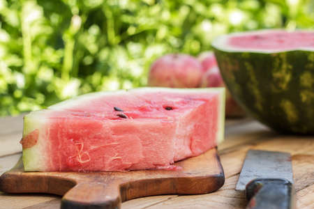 watermelon and old knife on the wooden table photo