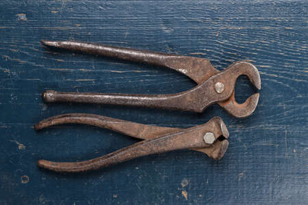 pinchers: old rusty tongs on blue wooden