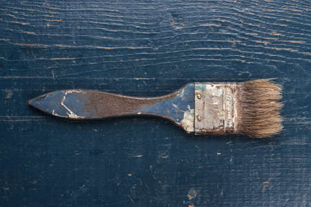 repaint: old brush on the blue wooden table Stock Photo
