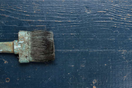 refurbishing: old brush on the blue wooden table Stock Photo