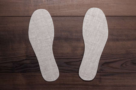 wooden insert: grey insoles for shoes over wooden  Stock Photo