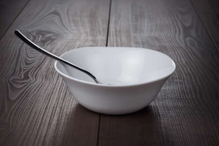 empty bowl with spoon on brown wooden table
