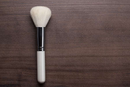 white make-up brush on brown wooden table photo