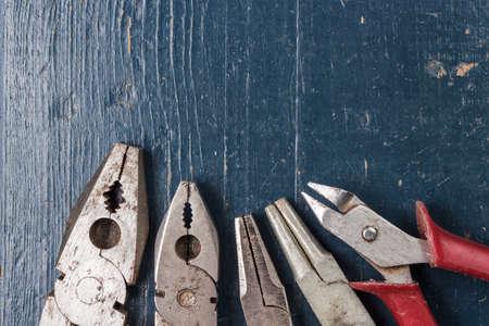 alicates: diferentes alicates en el fondo de madera azul