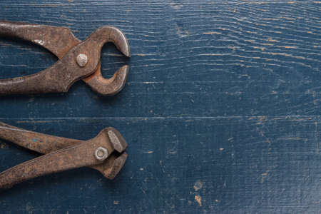 old rusty tongs on blue wooden background photo
