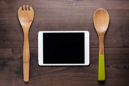 two wooden spoons and tablet computer on the brown table