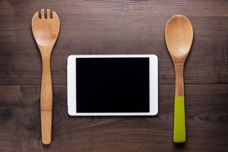 zwei Holzlöffel und Tablet-Computer auf dem braunen Tisch