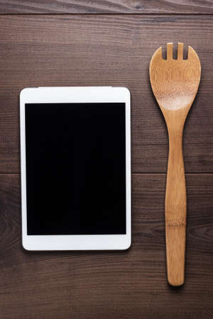 wooden spoon and tablet computer on the brown table photo