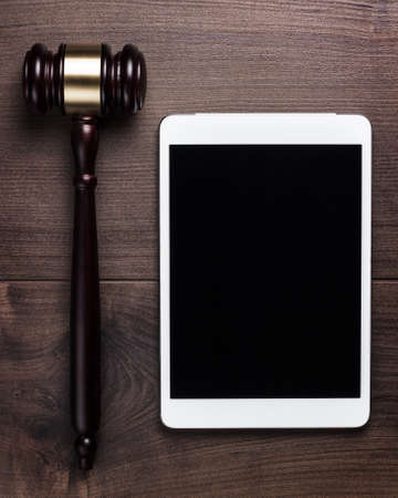 information technology law: judge gavel and tablet computer on table cyber crime concept Stock Photo