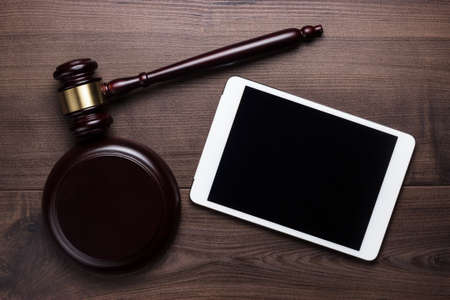 legal pad: judge gavel and tablet computer on table cyber crime concept Stock Photo