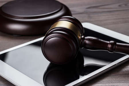 legal law: judge gavel and tablet computer on table cyber crime concept Stock Photo