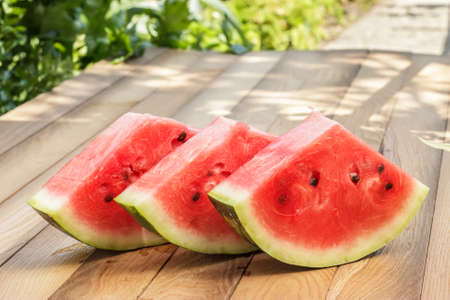 three watermelon pieces on the wooden table photo