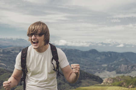happy man shouting at the mountain top photo