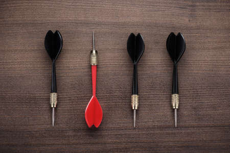 DARTS: red dart uniqueness concept on brown wooden background