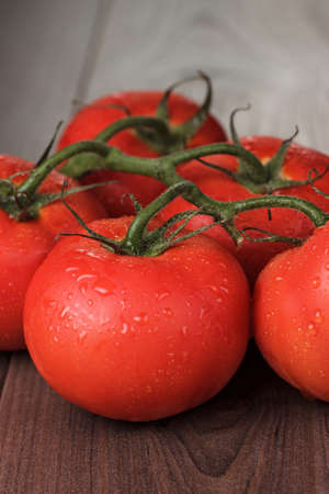 fresh red tomatoes on the brown wooden table photo