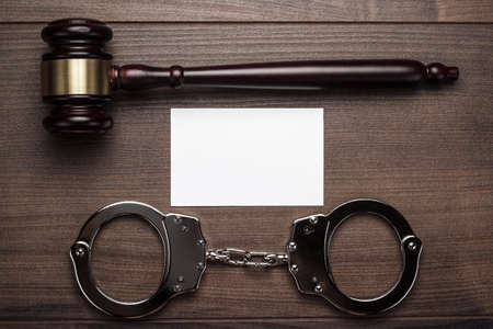 wristlets: handcuffs and judge gavel on brown wooden background Stock Photo