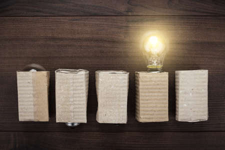 uniqueness: glowing bulb uniqueness concept on brown wooden background