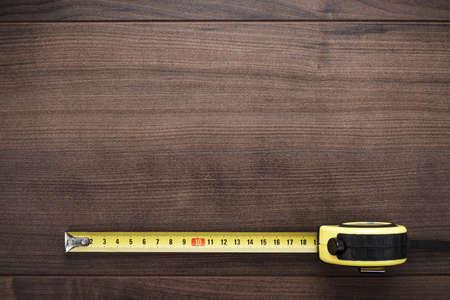 páska: svinovací metr na hnědé dřevěné pozadí Reklamní fotografie