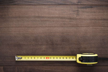 measure tape: tape measure on the brown wooden background