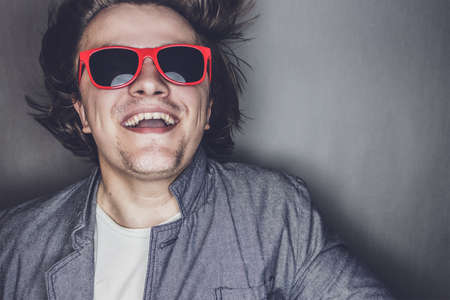 closeup portrait of a casual young man with sunglasses jumping Imagens