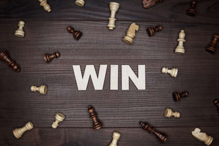 chessmen: word win and chessmen on the brown wooden background