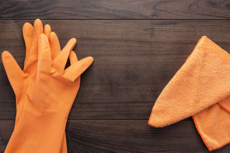 orange rubber cleaning gloves on wooden background photo