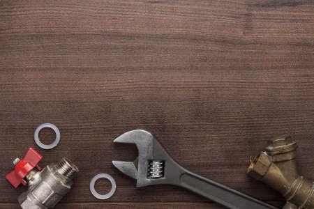 verstellbarer Schraubenschlüssel und Rohrleitungen auf dem hölzernen Hintergrund