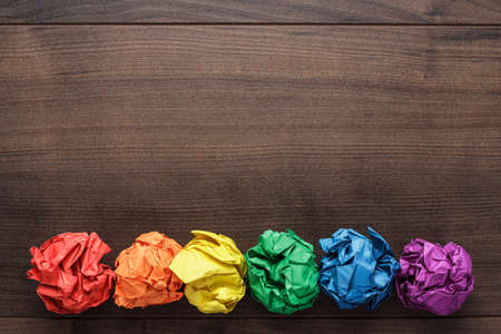 crumpled colorful paper on wooden background creative process Foto de archivo