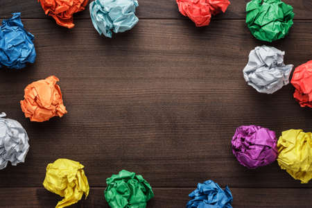 creative planning: crumpled colorful paper on wooden background creative process Stock Photo