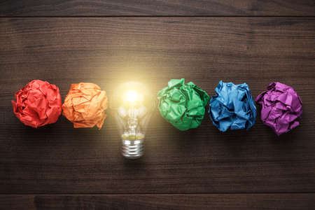 new ideas: great idea concept with crumpled colorful paper and light bulb on wooden table Stock Photo