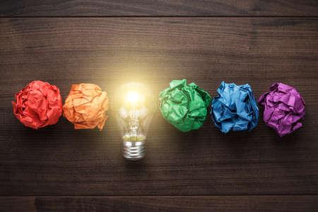 Úspěch: skvělý nápad koncepce s zmačkaný papír a barevné žárovky na dřevěném stole Reklamní fotografie