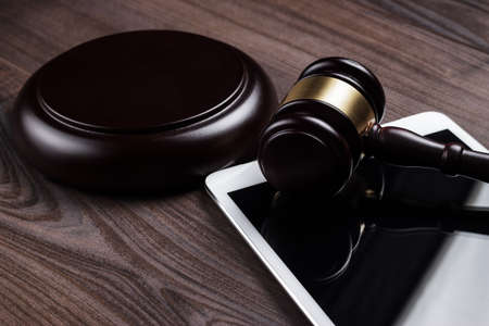 judge gavel and tablet computer on the table photo