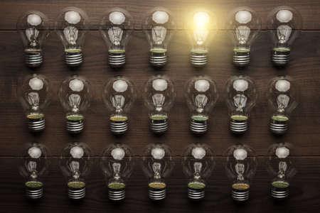 leuchtende Glühbirne Einzigartigkeit Konzept auf braunen Holztisch