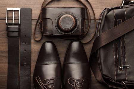 나무 테이블에 갈색 신발, 벨트, 가방 및 필름 카메라