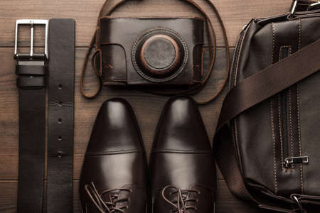 leather background: brown shoes, belt, bag and film camera on the wooden table Stock Photo