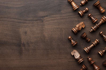 Schachfiguren auf dem braunen Holztisch Hintergrund Standard-Bild