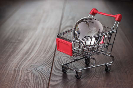 global market: glass globe in the shopping trolley global market concept