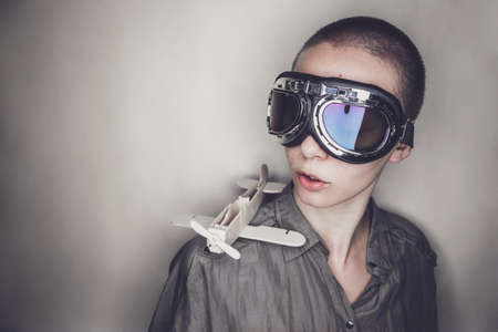 female soldier: short-haired girl in retro pilot glasses with wooden plane Stock Photo