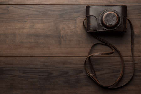 wooden background with retro still camera in case photo